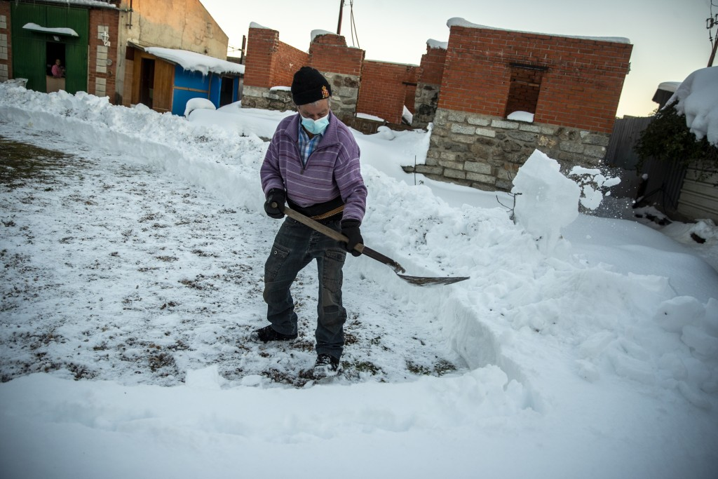 Emilio Lopez Jimenez, 79, clears the snow of his house at the Canada Real shanty town, outside Madrid, Spain, Friday, Jan. 8, 2021. As a record snowfa...