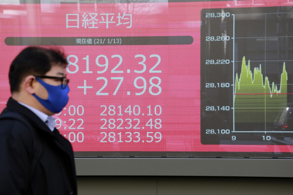 A man walks by an electronic stock board of a securities firm in Tokyo, Wednesday, Jan. 13, 2021. Asian stock markets were mixed Wednesday after Wall ...