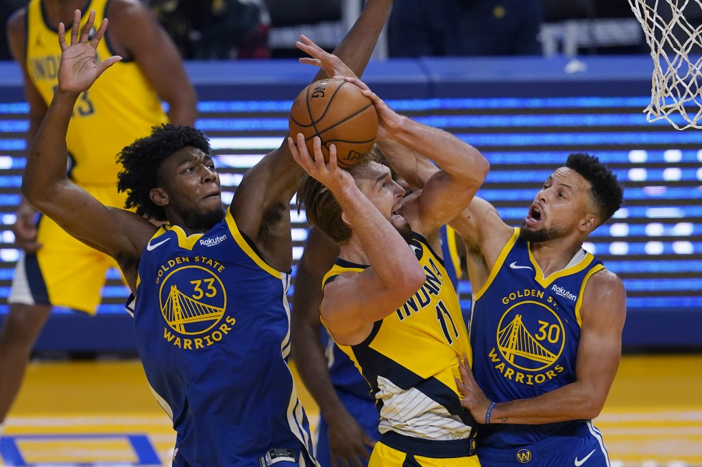 Indiana Pacers forward Domantas Sabonis, middle, shoots between Golden State Warriors center James Wiseman (33) and guard Stephen Curry (30) during th...