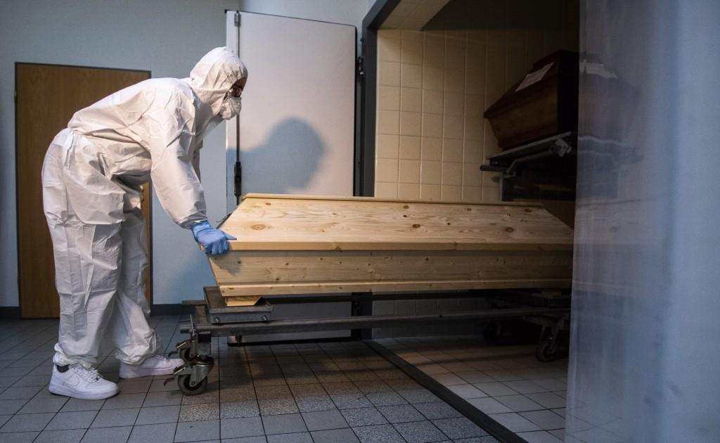 """Employee Niklas Grube pushes a coffin into a cooling chamber at the crematorium """"Die Feuerbestattungen Celle"""", in Celle, Germany, Wednesday, Jan. 13, ..."""