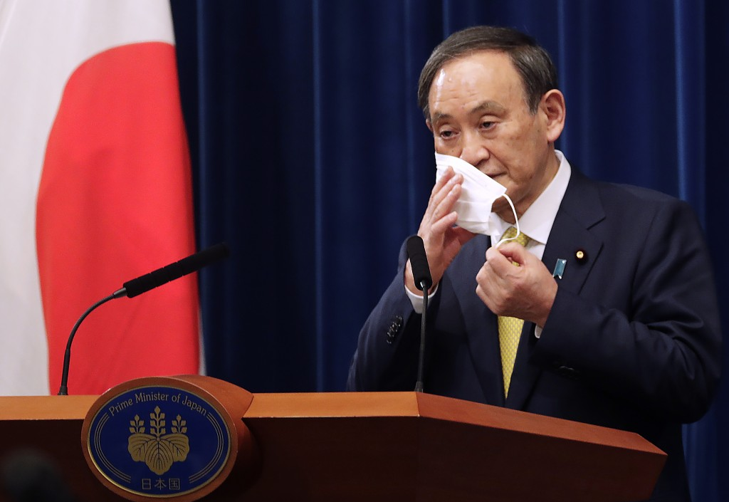 FILE - In this Dec. 4, 2020, file photo, Japanese Prime Minister Yoshihide Suga removes his face mask during a news conference in Tokyo. Opposition to...