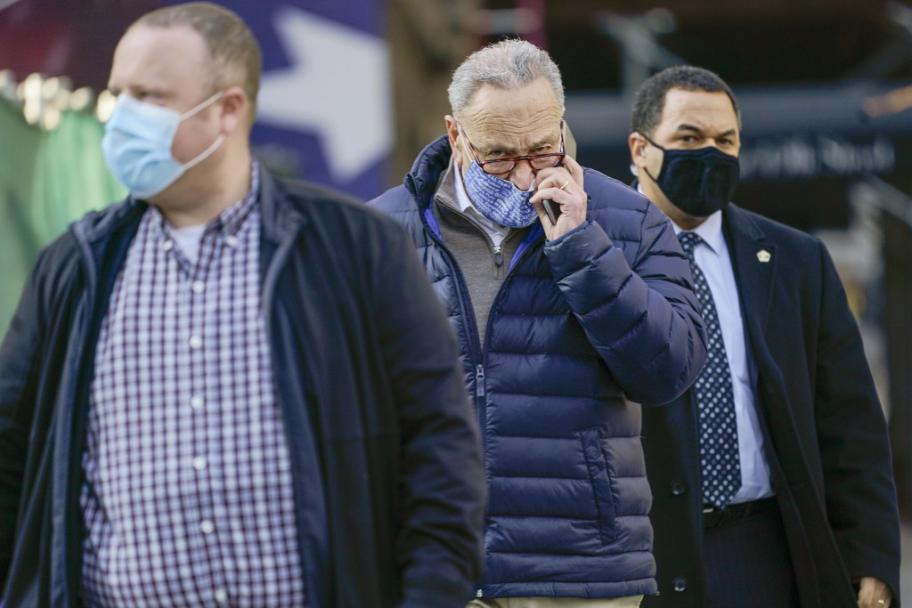 Senate Minority Leader Chuck Schumer, D-N.Y., center, is surrounded by security as he arrives for a news conference, Tuesday, Jan. 12, 2021, in New Yo...