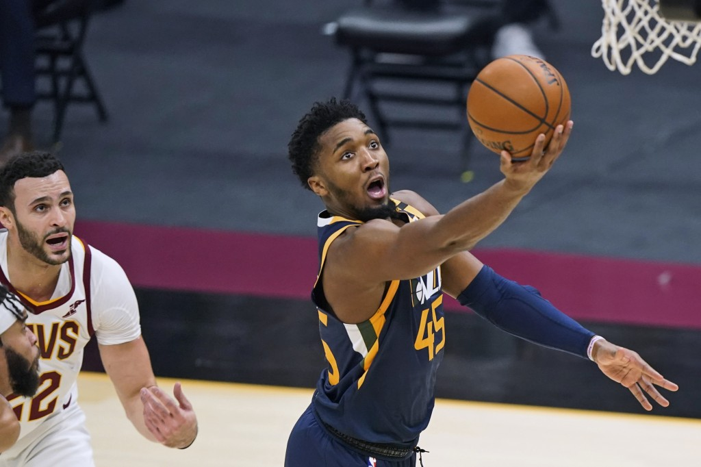 Utah Jazz's Donovan Mitchell (45) drives to the basket as Cleveland Cavaliers' Larry Nance Jr. watches during the first half of an NBA basketball game...