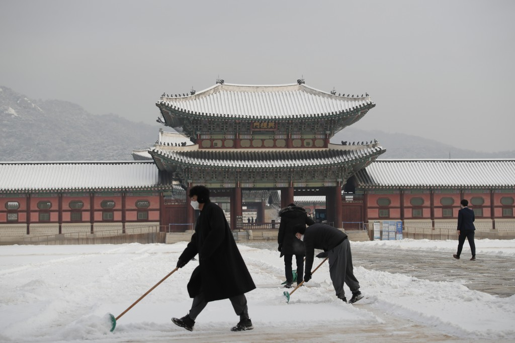 People wearing face masks as a precaution against the coronavirus clear snow at the Gyeongbok Palace, one of South Korea's well-known landmarks, in Se...