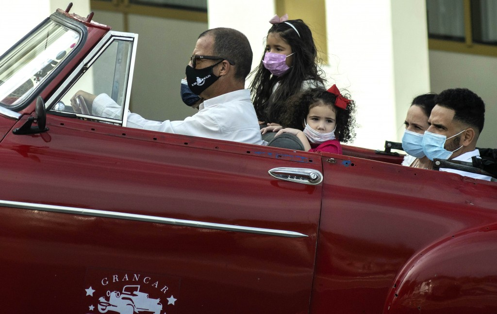 People wearing masks as a precaution against the spread of the new coronavirus, travel in a classic American car in Havana, Cuba, Tuesday, Jan. 12, 20...