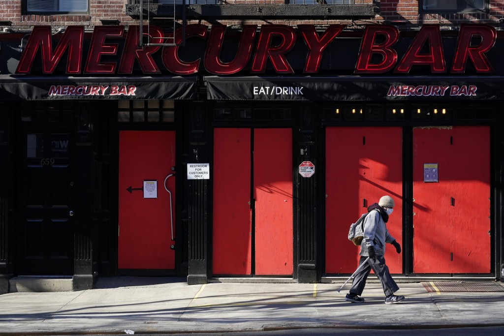 FILE - In this Jan. 10, 2021, file photo, a pedestrian walks past a boarded-up bar in the Hell's Kitchen neighborhood of New York. The boarded-up wind...