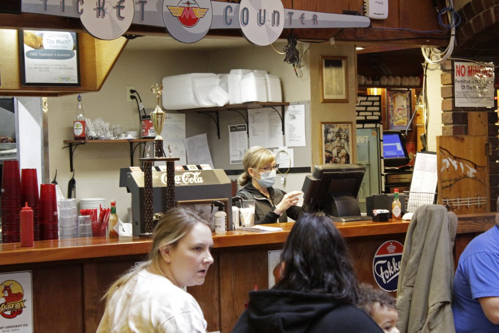 Restaurant co-owner Liz Mitchell works behind the bar at the Carver Hangar in Boring, Ore., on Jan. 6, 2021. As coronavirus deaths soar, a growing num...