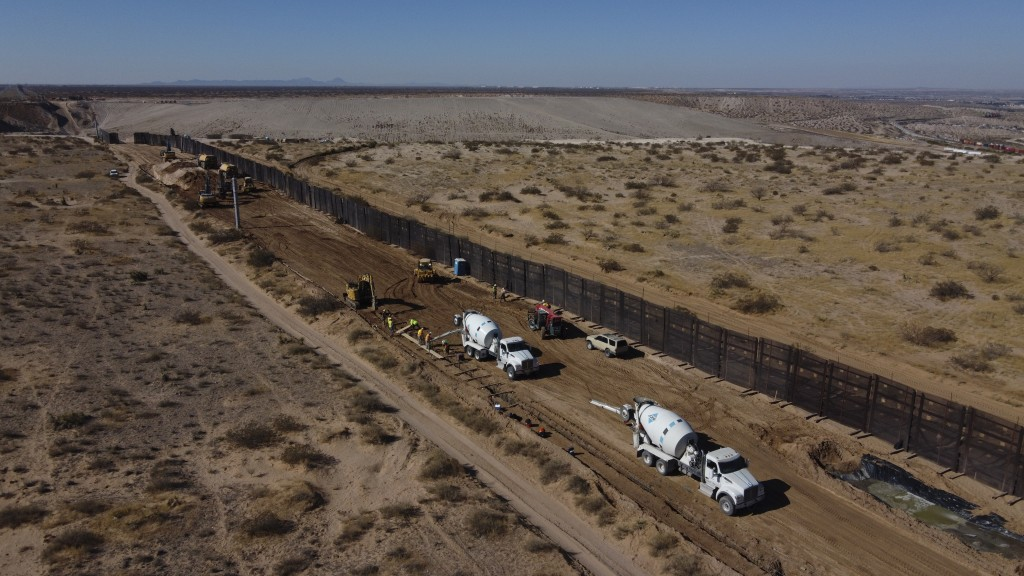 Workers prepare the foundation for a steel section of border wall that will be built on the Mexican side of older metal fencing dividing Ciudad Juarez...