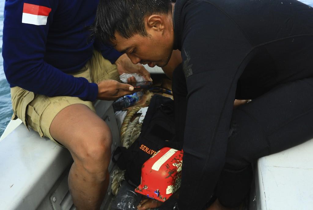 Indonesian Navy divers examine the flight data recorder of Sriwijaya Air flight SJ-182 retrieved from the waters off Java Island where the passenger j...