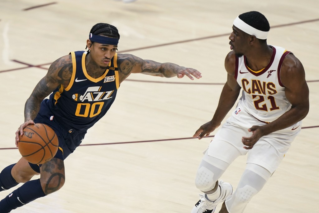 Utah Jazz's Jordan Clarkson (00) drives past Cleveland Cavaliers' Damyean Dotson (21) during the first half of an NBA basketball game Tuesday, Jan. 12...