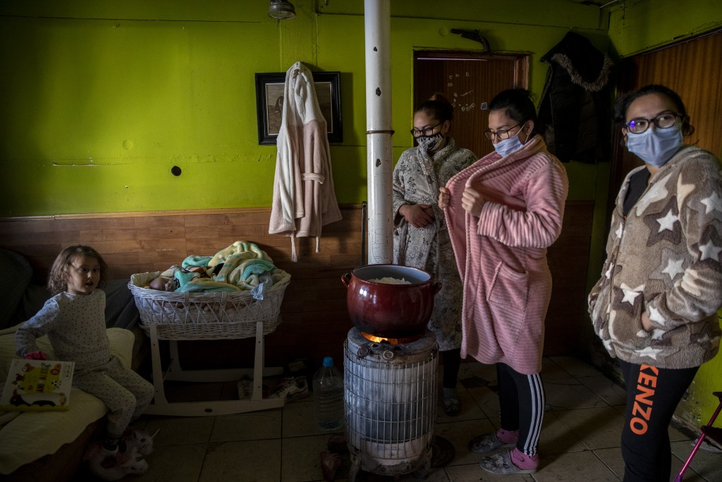 Family members of baby Jesus Fernandez, one month old, melt snow in a pot at the Canada Real shanty town, outside Madrid, Spain, Tuesday, Jan. 12, 202...