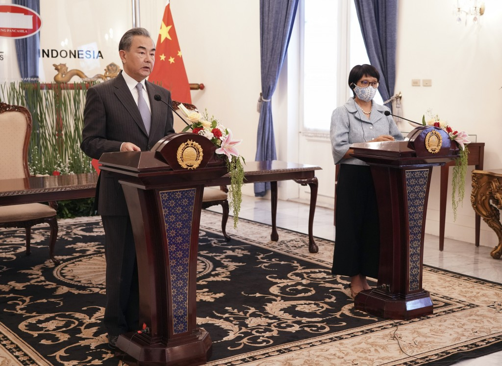 In this photo released by Indonesian Foreign Ministry, Chinese Foreign Minister Wang Yi, left, talks to the media as his Indonesian counterpart Retno ...