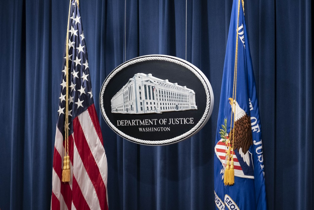 A sign for the Department of Justice is seen ahead of a news conference Tuesday, Jan. 12, 2021, in Washington. Federal prosecutors are looking at brin...