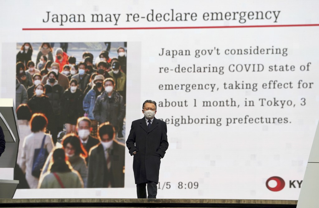 FILE - In this Jan. 5, 2021, file photo, a man wearing a mask against the spread of the coronavirus walks in front of a screen showing the news on pos...