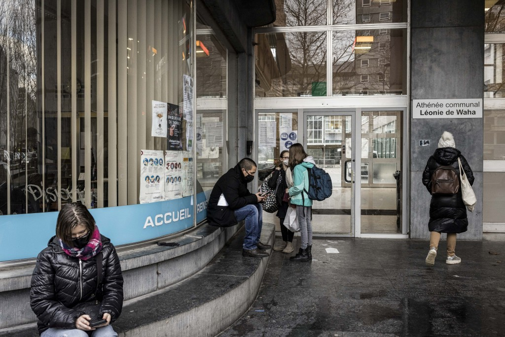 Students and relatives stand at the main entrance of the school Athenee Leonie de Waha in Liege, Belgium, Tuesday, Jan. 12, 2021. Fed up with the COVI...