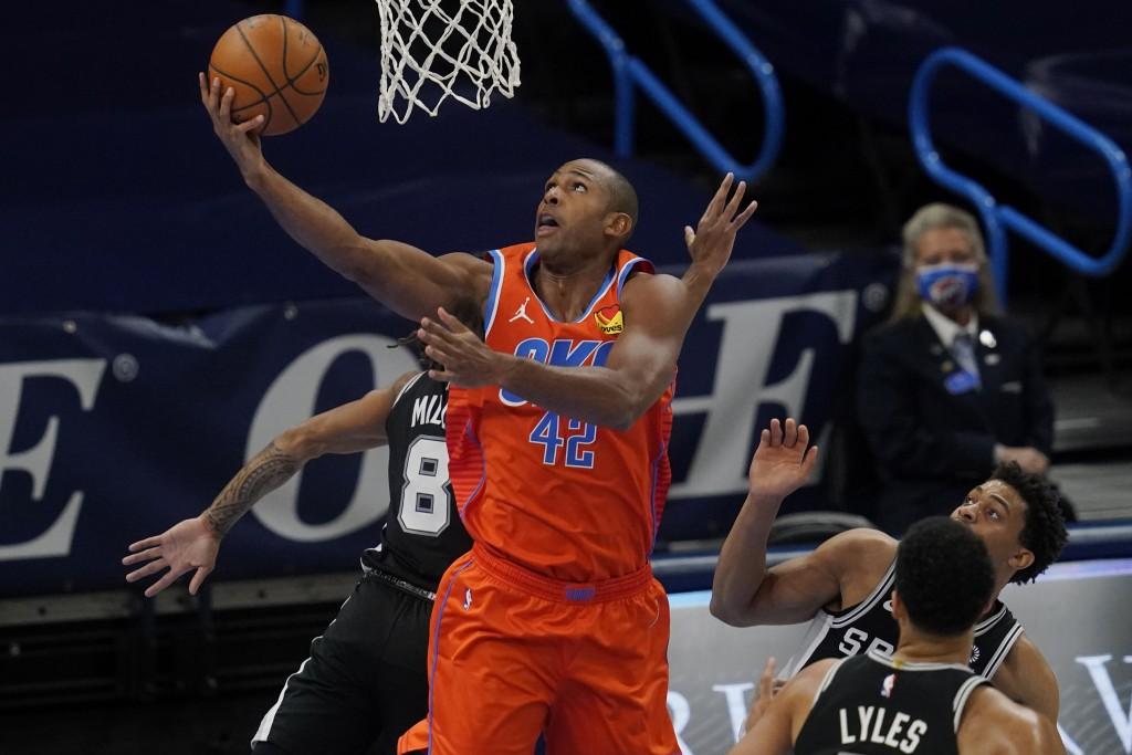Oklahoma City Thunder center Al Horford (42) shoots between San Antonio Spurs guard Patty Mills (8), forward Trey Lyles and forward Keldon Johnson, ba...