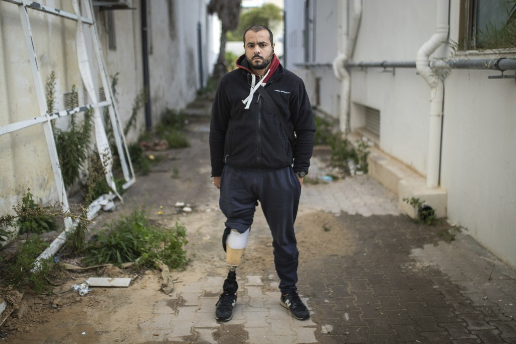 Walid Kasraoui, 32, a protester who lost a leg after getting shot during Tunisia's democratic uprising 10 years ago, poses for a portrait in Tunis, Tu...