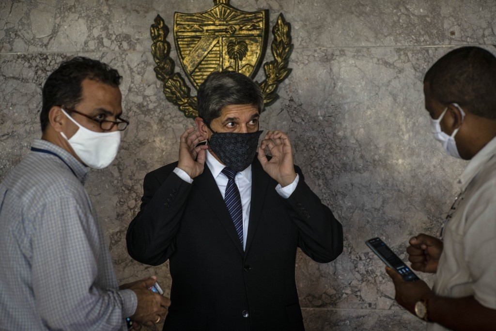 Cuba's Director General of U.S. Affairs Carlos Fernández de Cossio, center, puts on a mask as a precaution against the spread of the new coronavirus, ...