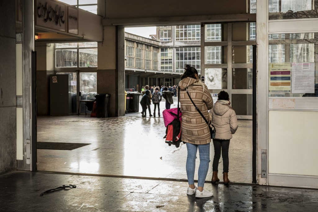 A woman and a child stand at the main entrance of the school Athenee Leonie de Waha in Liege, Belgium, Tuesday, Jan. 12, 2021. Fed up with the COVID-1...