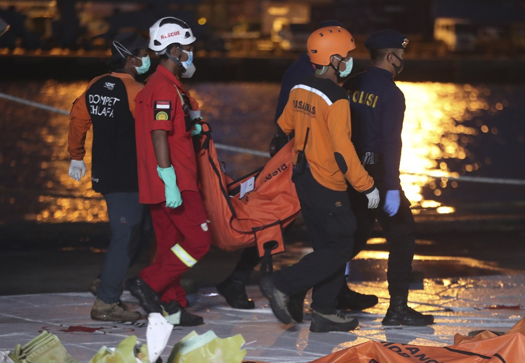 Indonesian rescue and police teams carry debris recovered from the crashed Sriwijaya Air passenger jet at the command center at Tanjung Priok Port in ...