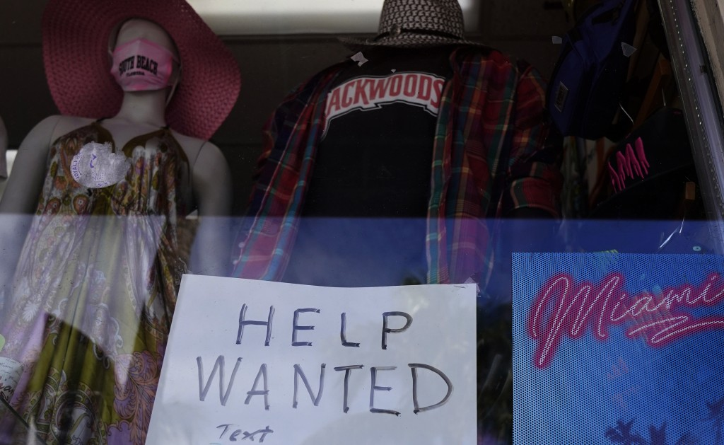 """A """"Help Wanted,"""" sign is shown in the window of a souvenir shop, Thursday, Jan. 7, 2021, in Miami Beach, Fla.  Layoffs spiked in November compared wit..."""
