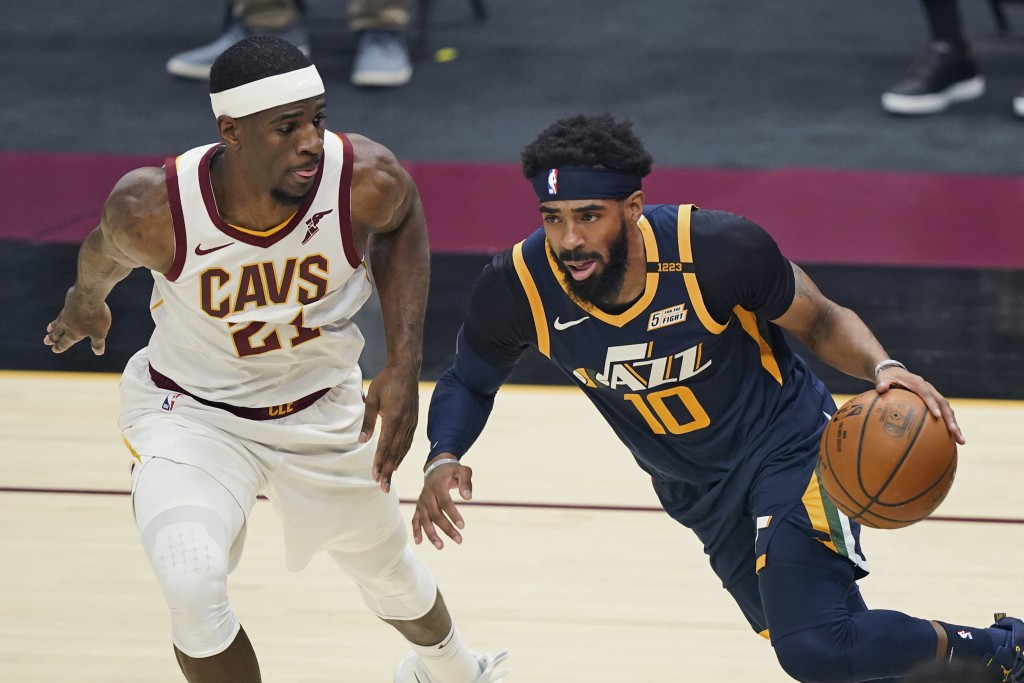 Utah Jazz's Mike Conley (10) drives past Cleveland Cavaliers' Damyean Dotson during the first half of an NBA basketball game Tuesday, Jan. 12, 2021, i...