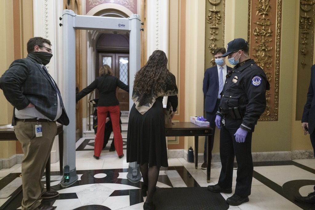 Congressional staff passes through a metal detector and security screening as they enter the House chamber, new measures put into place after a mob lo...