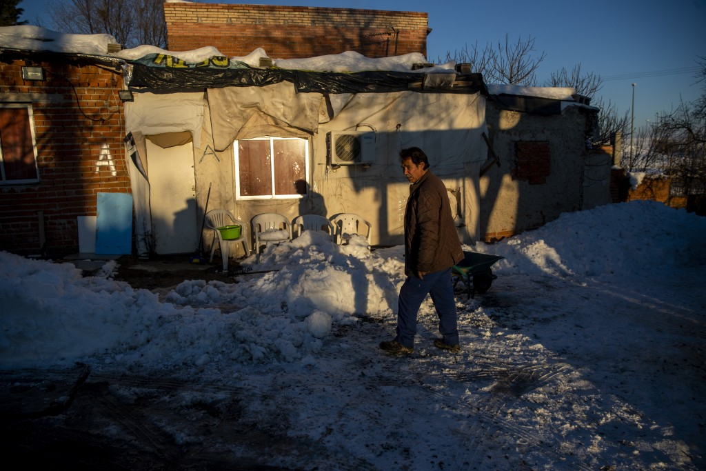 A man walks in front of his house covered with snow at the Canada Real shanty town, outside Madrid, Spain, Tuesday, Jan. 12, 2021. Ranked as one of th...