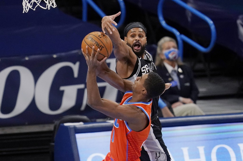 Oklahoma City Thunder guard Theo Maledon, front, goes to the basket as San Antonio Spurs guard Patty Mills defends during the first half of an NBA bas...