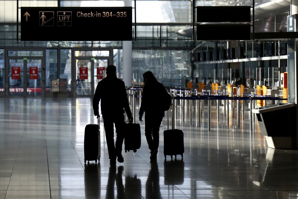 FILE - In this Saturday, Dec. 26, 2020 file photo, people walk with their luggage through a deserted check-in hall at the airport in Munich, Germany a...