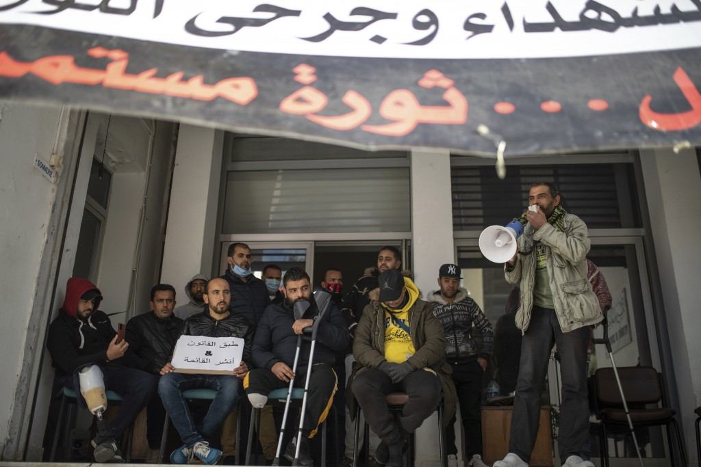 People who were injured during Tunisia's democratic uprising 10 years ago, stage a protest demanding official recognition, in Tunis, Tunisia, Tuesday,...