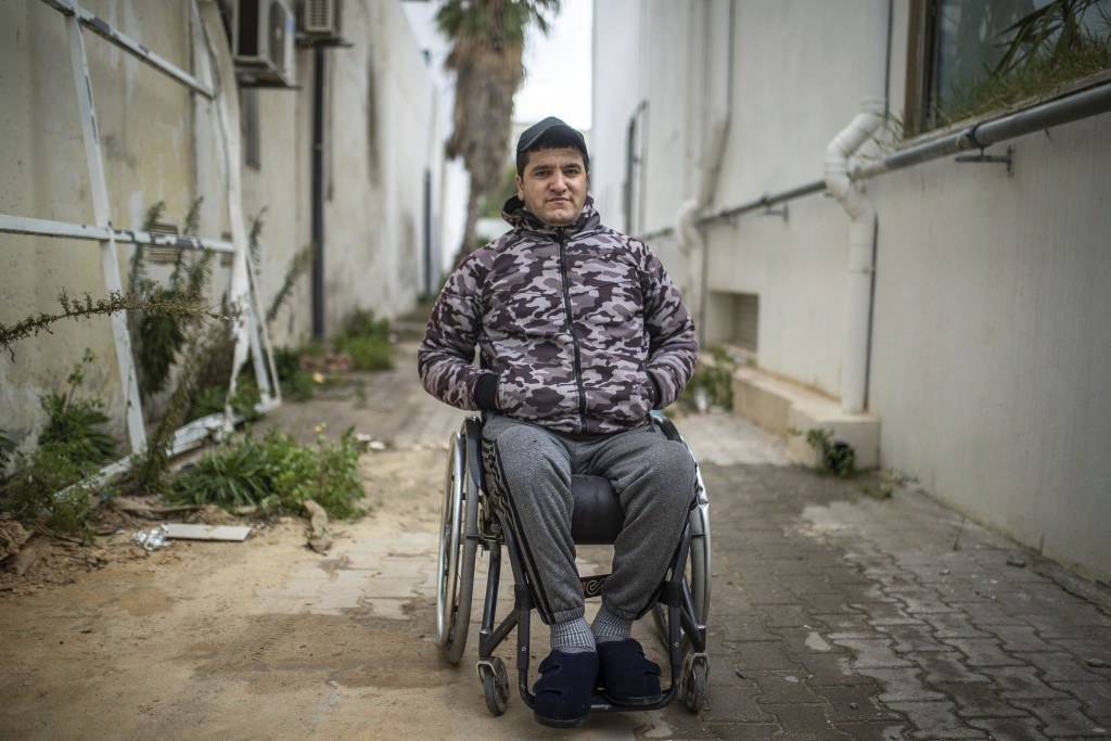 Khaled Benneejma, 32, a protester who was paralyzed after being shot during Tunisia's democratic uprising 10 years ago, poses for a portrait in Tunis,...