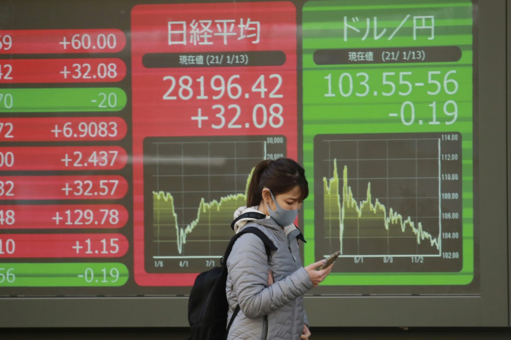 A woman walks by an electronic stock board of a securities firm in Tokyo, Wednesday, Jan. 13, 2021. Asian stock markets were mixed Wednesday after Wal...