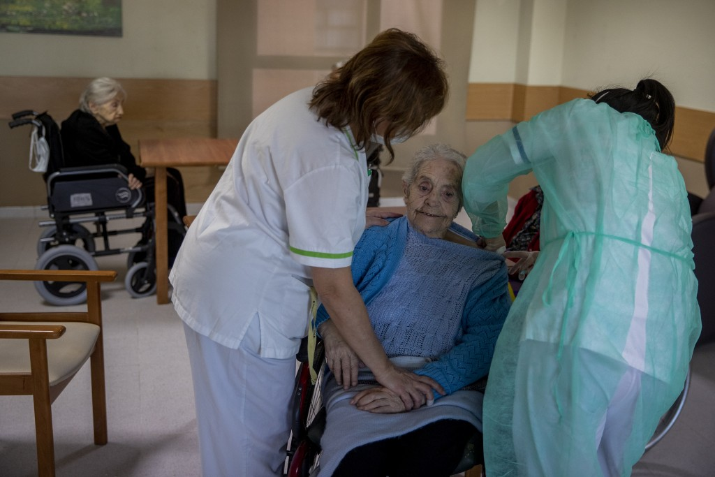 A nurse administers the Pfizer-BioNTech COVID-19 vaccine to a resident at DomusVi nursing home in Leganes, Spain, Wednesday, Jan. 13, 2021. Spain's ra...