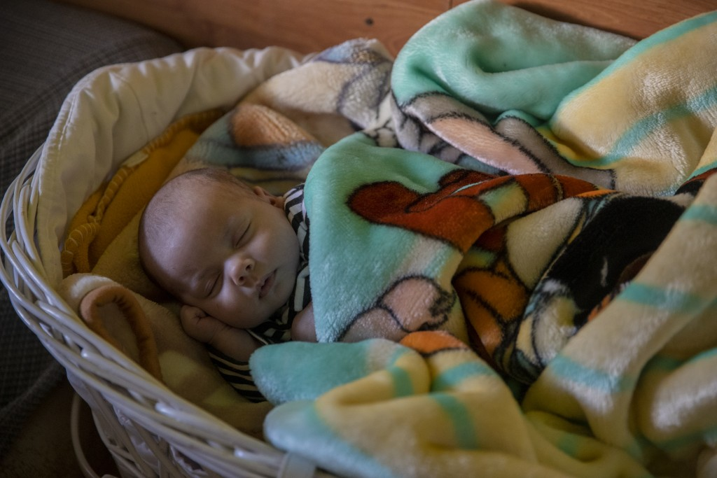 Baby Jesus Fernandez, one month old, sleeps at the Canada Real shanty town, outside Madrid, Spain, Tuesday, Jan. 12, 2021. As a record snowfall blanke...