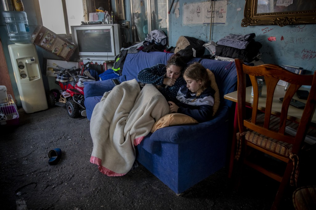 A woman rests with her daughter inside their home at the Canada Real shanty town, outside Madrid, Spain, Tuesday, Jan. 12, 2021.  Shops are flimsy set...