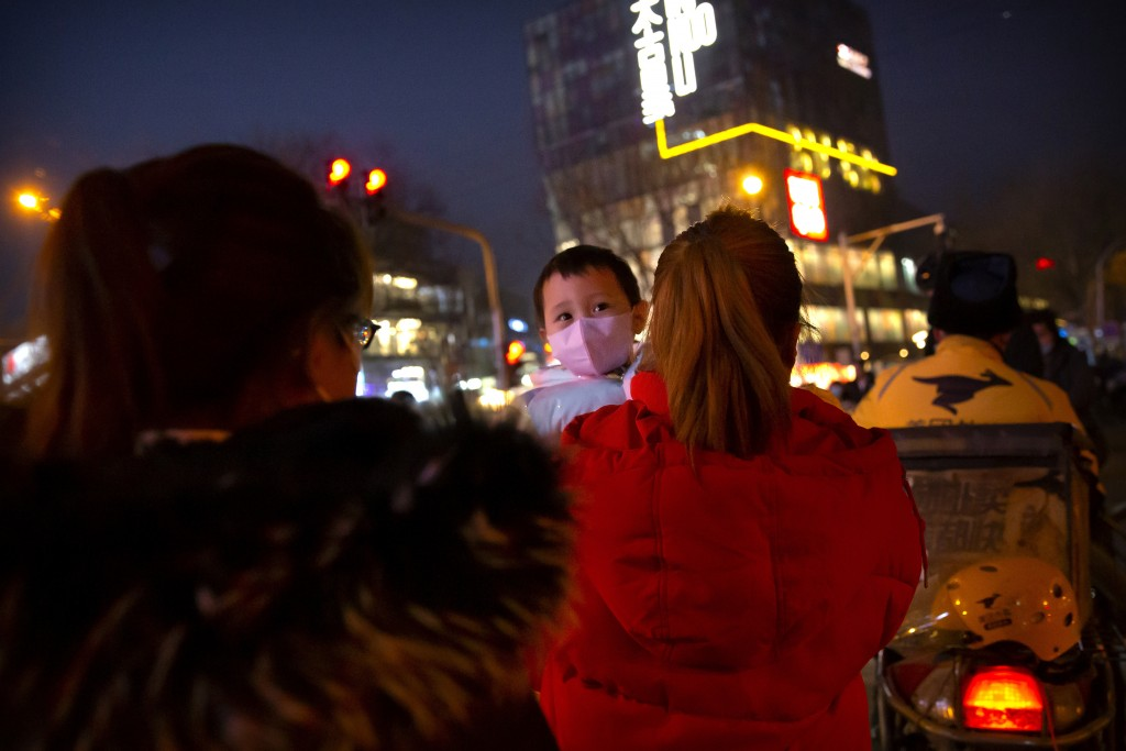 A woman carries a child wearing a face mask to protect against the spread of the coronavirus as they walk across an intersection in Beijing, Wednesday...