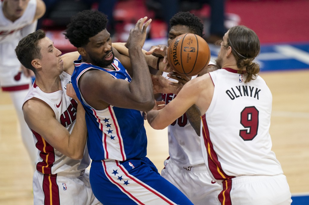 Philadelphia 76ers' Joel Embiid, center left, is defended by Miami Heat's Duncan Robinson, left, Chris Silva, center right, and Kelly Olynyk during th...