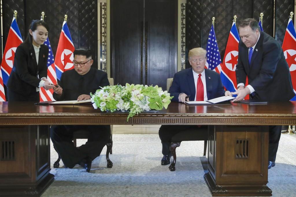 FILE - In this June 12, 2018, file photo, North Korea leader Kim Jong Un, center left, and U.S. President Donald Trump, center right, prepare to sign ...