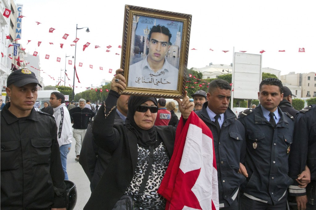 FILE - In this April 9, 2012 file photo, a Tunisian woman holds a poster of her martyr son named Helmi Manaai, written under the photo, during a prote...