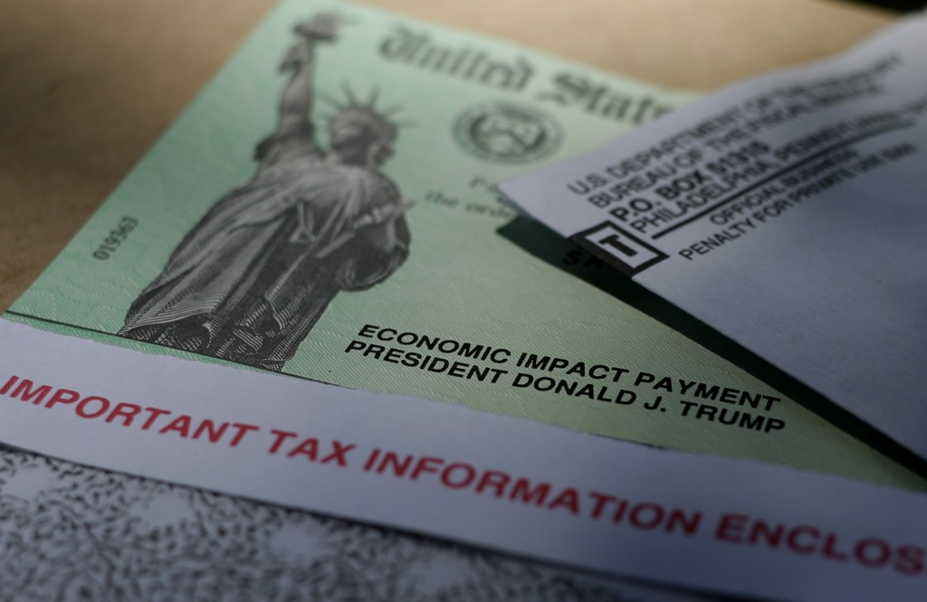 FILE - In this April 23, 2020 file photo, President Donald J.Trump's name is printed on a stimulus check issued by the IRS to help combat the adverse ...