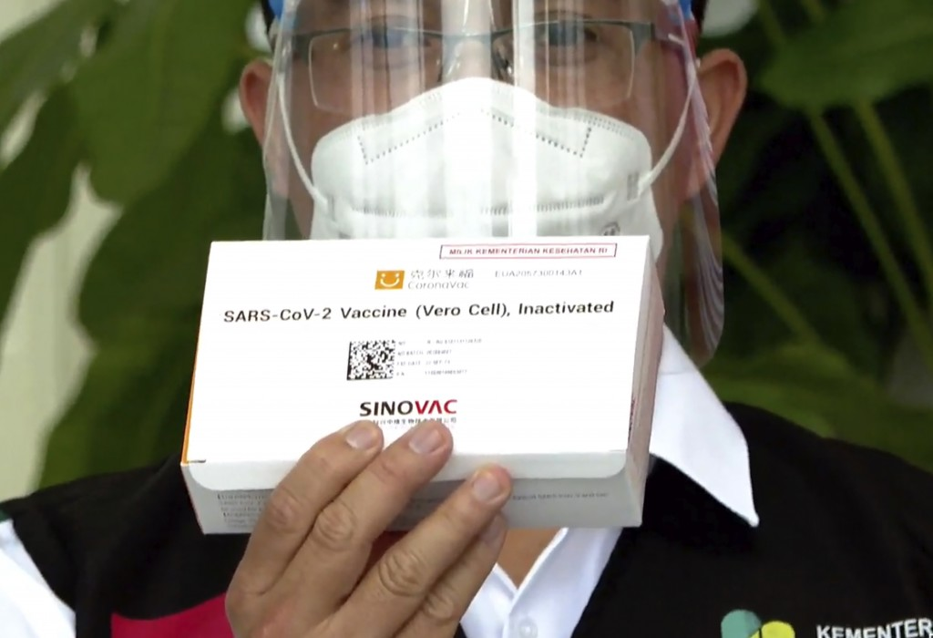 In this image made from a video released by Indonesian Presidential Palace, a Health Ministry official shows a box of COVID-19 vaccine that will be gi...