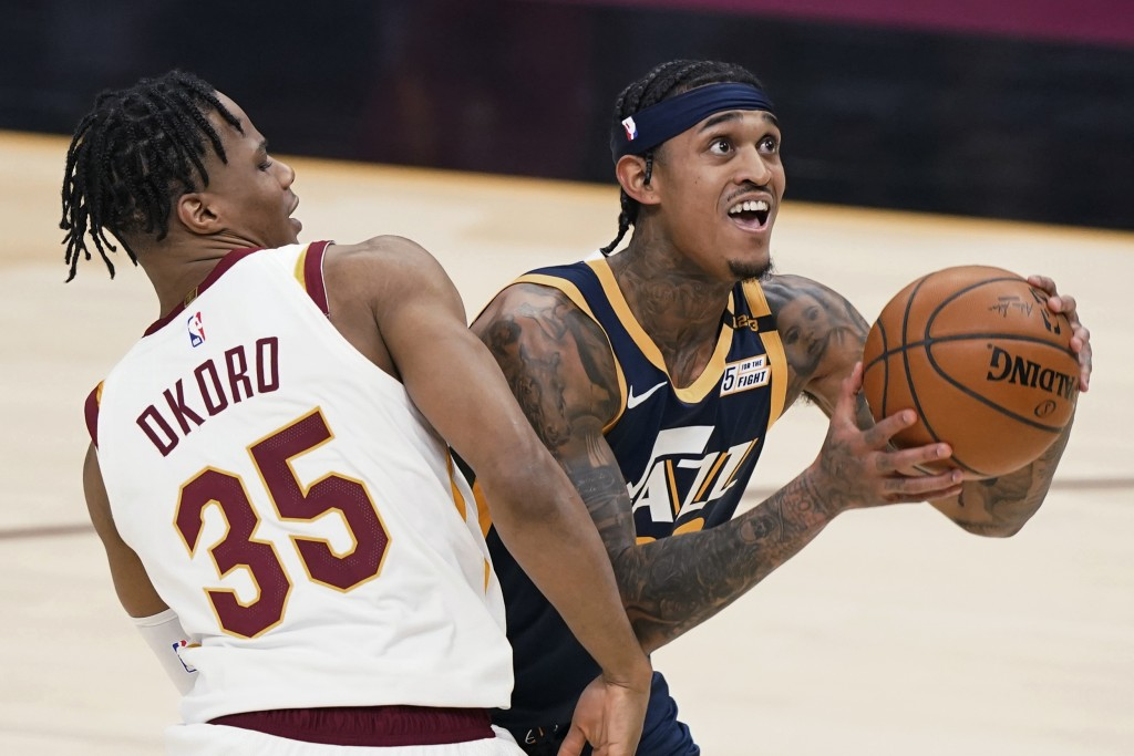 Utah Jazz's Jordan Clarkson, right, drives to the basket against Cleveland Cavaliers' Isaac Okoro during the first half of an NBA basketball game Tues...