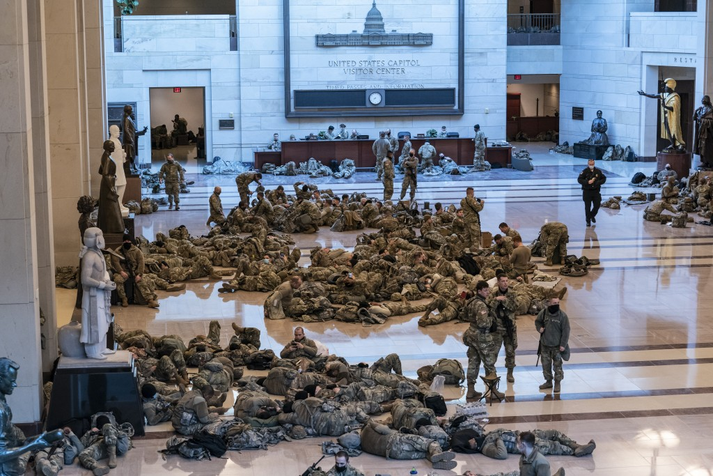Hundreds of National Guard troops hold inside the Capitol Visitor's Center to reinforce security at the Capitol in Washington, Wednesday, Jan. 13, 202...