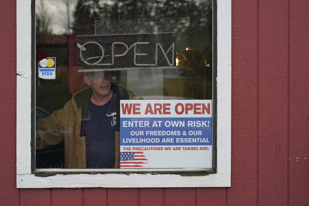 FILE - In this Jan. 4, 2021, file photo, a person walks through an entrance to the Farm Boy Drive-In restaurant during a protest rally near Olympia, W...