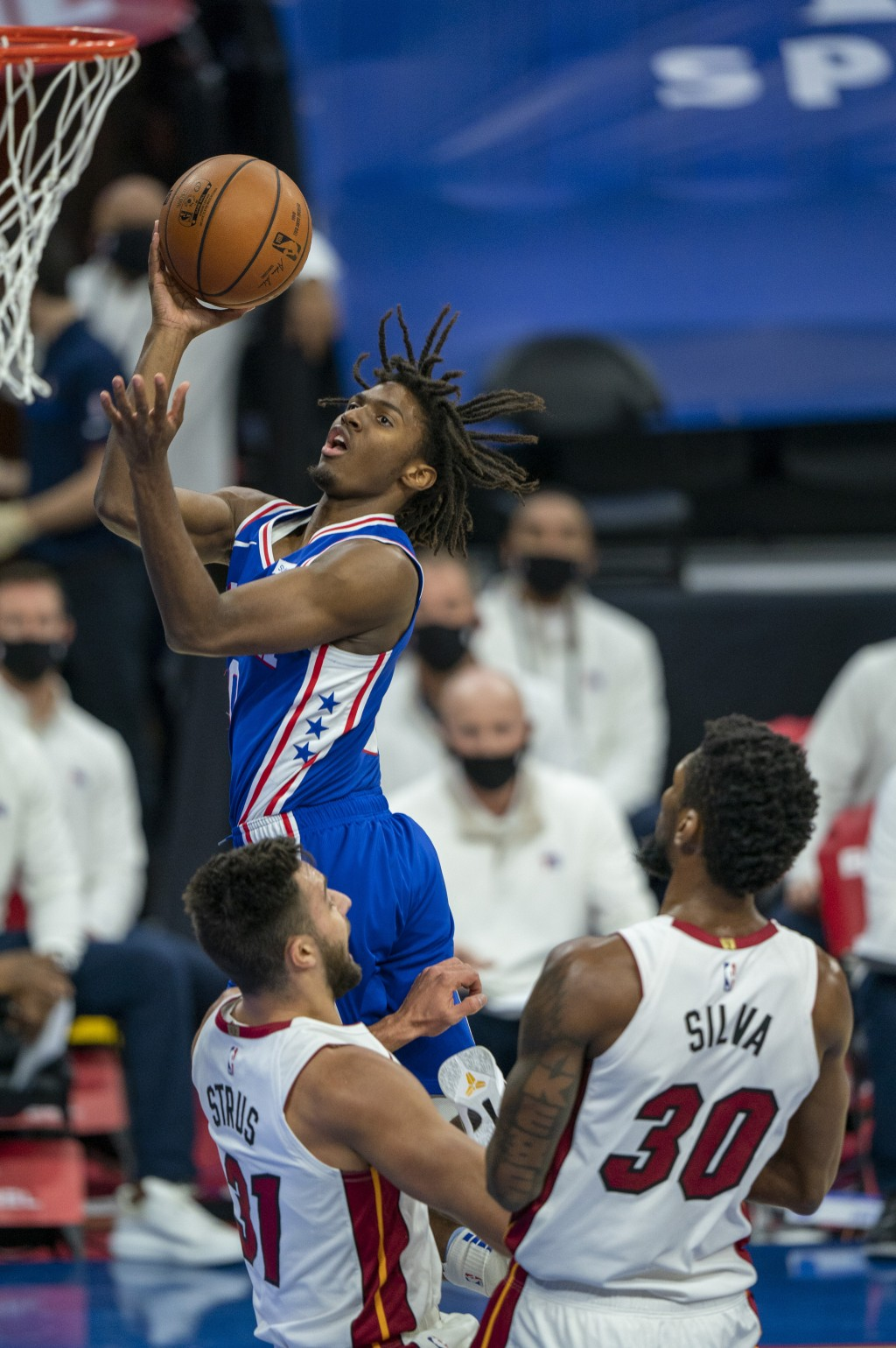 Philadelphia 76ers' Tyrese Maxey goes up for the shot as he is fouled by Miami Heat's Chris Silva, right, and runs into Max Strus, left, during the fi...