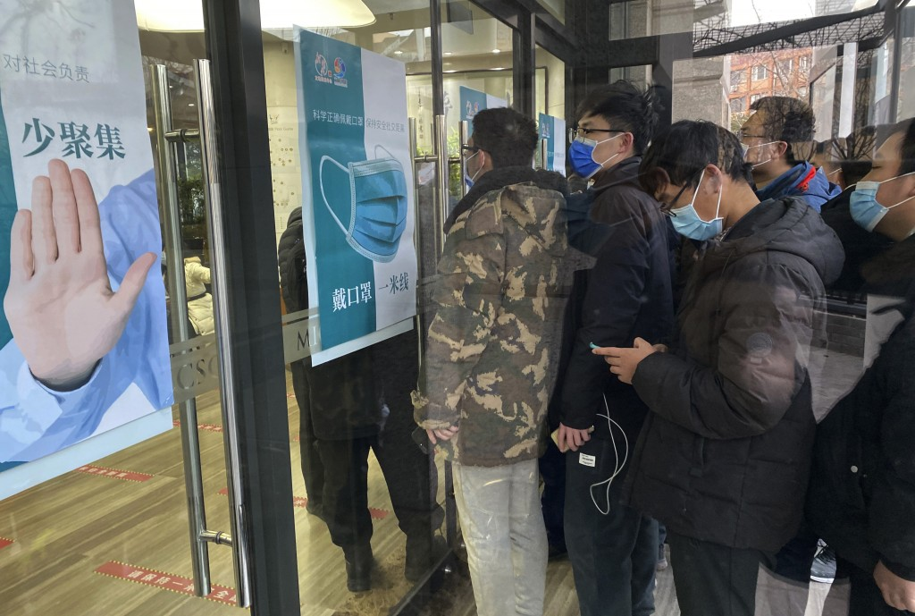 """Locals line up for COVID-19 vaccinations near a poster with the slogan """"Avoid Gatherings"""" in Beijing on Tuesday, Jan. 12, 2021. China announced over t..."""