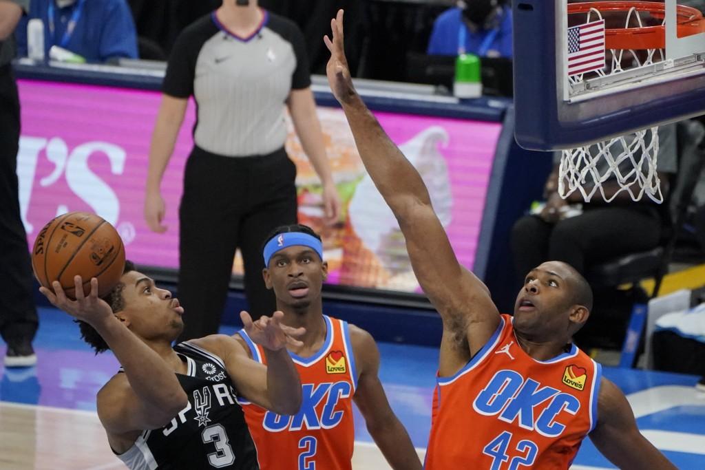 San Antonio Spurs forward Keldon Johnson (3) goes to the basket in front of Oklahoma City Thunder guard Shai Gilgeous-Alexander (2) and center Al Horf...