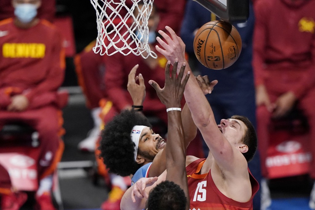 Brooklyn Nets center Jarrett Allen, left, defends against Denver Nuggets center Nikola Jokic (15) during the first quarter of an NBA basketball game T...