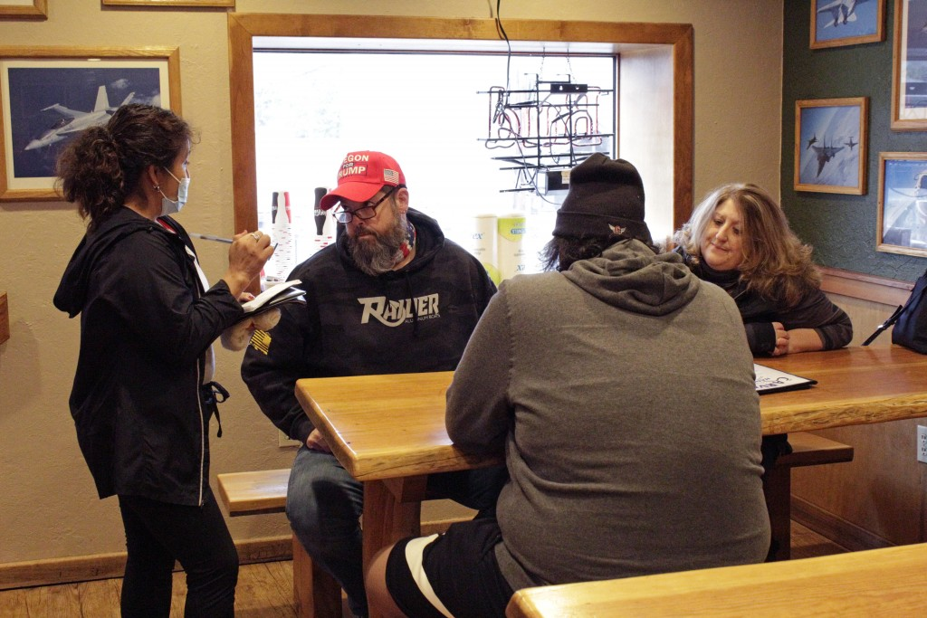 A waitress takes orders from unmasked customers at the Carver Hangar, a restaurant in Boring, Ore., on Jan. 6, 2021. As coronavirus deaths soar, a gro...